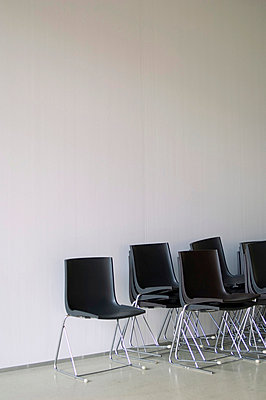 Stacked black chairs in front of a white wall - p4902815 by Jan Mammey