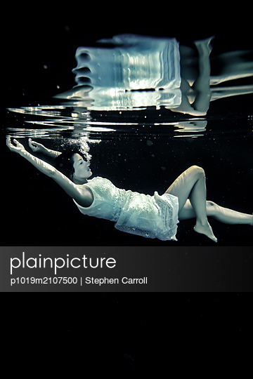 Underwater View of Woman Floating - p1019m2107500 by Stephen Carroll