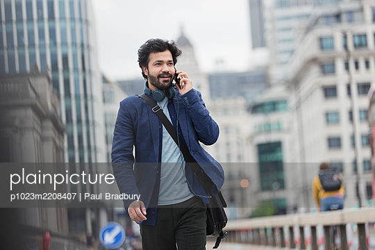 Businessman talking on smart phone in city - p1023m2208407 by Paul Bradbury