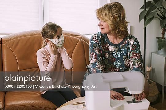 Mature woman looking at granddaughter wearing homemade face mask - p300m2203158 by Viktoriya Birkholz Photography Art