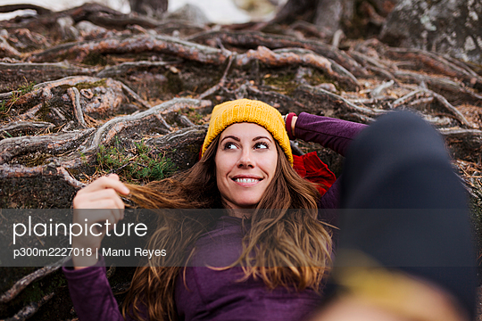 Smiling woman looking away while lying on tree roots in forest at La Pedriza, Madrid, Spain - p300m2227018 by Manu Reyes