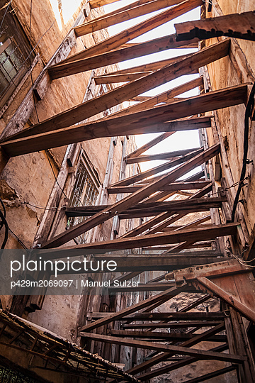 Wooden beams between and supporting buildings, low angle view,  Fes, Morocco - p429m2069097 by Manuel Sulzer