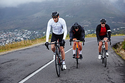 Dedicated male cyclists cycling on uphill road - p1023m1584010 by Richard Johnson