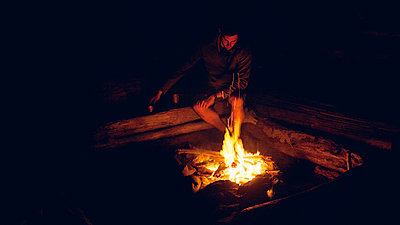 Man sitting by bonfire at night - p1166m1154159 by Cavan Images