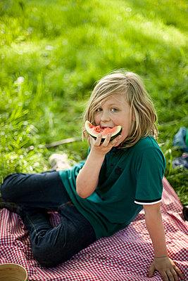 Boy eating melon at a picnic - p1195m1138153 by Kathrin Brunnhofer