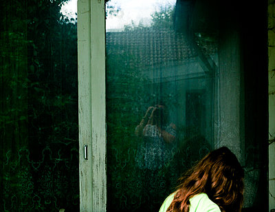 Woman reflecting in window - p1279m1466888 by Ulrike Piringer
