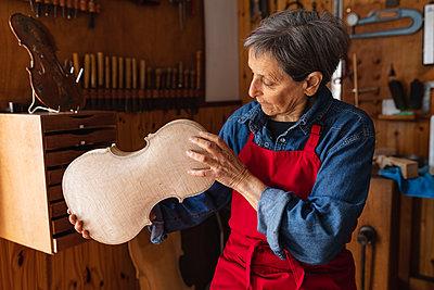 Female luthier at work in a workshop - p1315m2131473 by Wavebreak