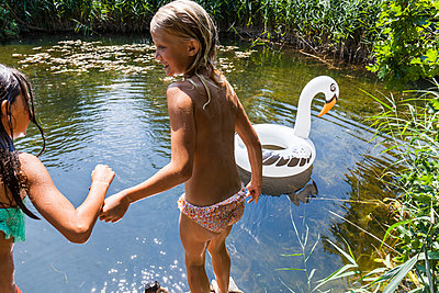 Two girls at a pond with inflatable pool toy in swan shape - p300m2030477 by Tom Chance