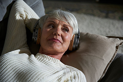 Portrait of senior woman relaxing on couch listening music with headphones - p300m2180055 by Stefanie Aumiller