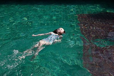 Girl floating in pool - p429m2098387 by Janeycakes Photos