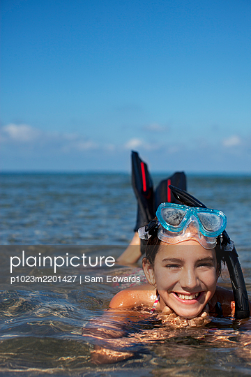 Smiling girl with snorkel and goggles laying in ocean - p1023m2201427 by Sam Edwards