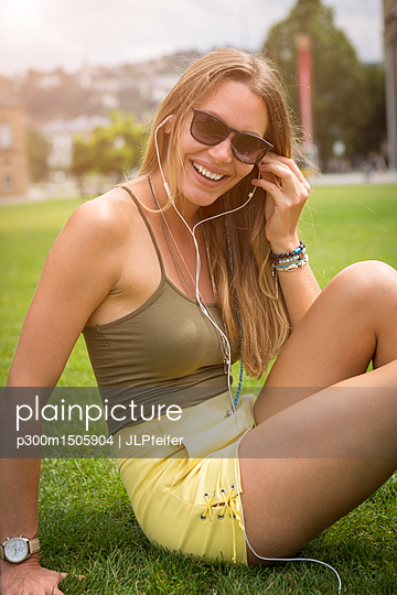 Happy young woman with earphones relaxing on lawn in park