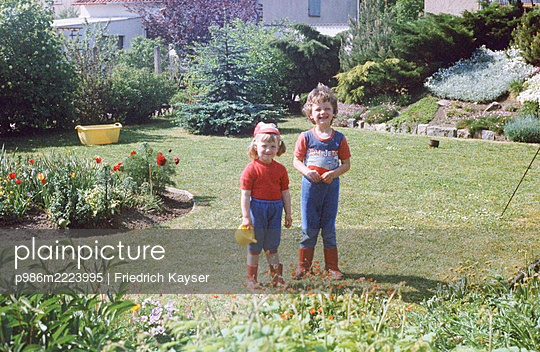 Germany, Siblings in the garden in the GDR - p986m2223995 by Friedrich Kayser