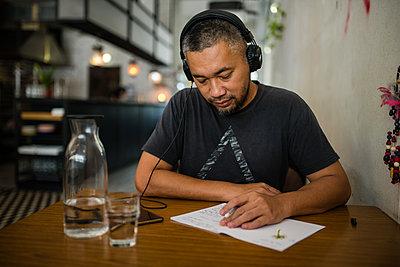 Asian man listening music on headphones - p1166m2131271 by Cavan Images