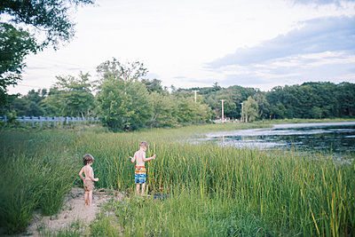 Two soaked children standing in the tall grasses by a lake - p1166m2202050 by Cavan Images