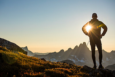 Sun shines through arm of silhouetted hiker on mountain ridge - p1166m2212416 by Cavan Images