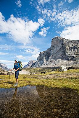 Backpacker standing below Mount Thor, Baffin ISland. - p1166m2261216 by Cavan Images