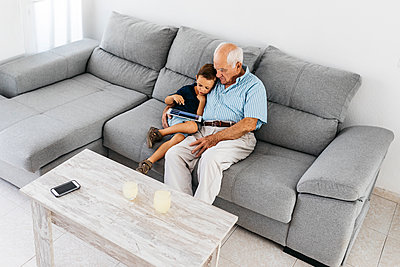 Grandfather and grandson sitting together on the couch at home looking at digital tablet - p300m2029513 von Josep Rovirosa
