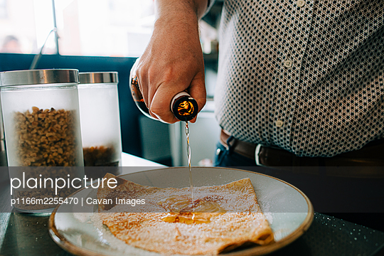 Hand of a man pouring sweet syrup on top of pancake on a plate - p1166m2255470 by Cavan Images