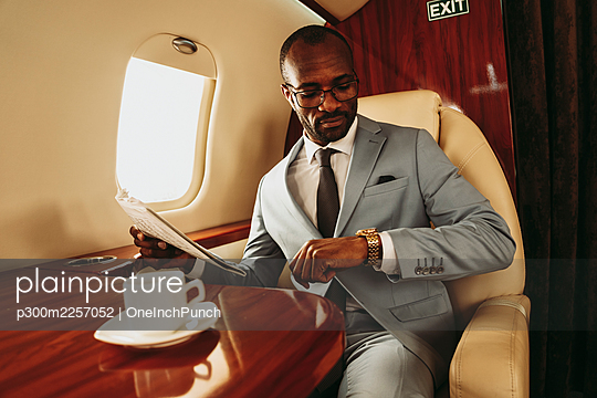 Businessman holding newspaper while checking time on wristwatch in airplane - p300m2257052 by OneInchPunch
