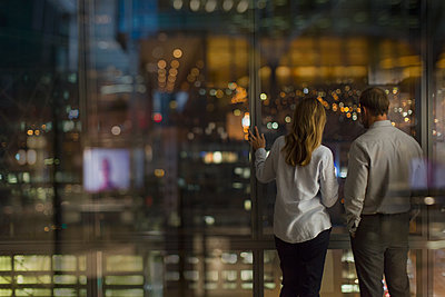 Businessman and businesswoman looking out urban office window at night - p1023m1518113 by Tom Merton