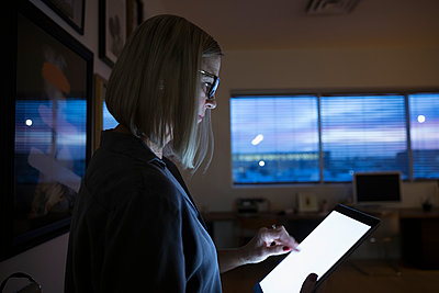 Senior businesswoman using digital tablet, working late - p1192m1529958 by Hero Images