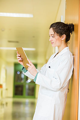 Young doctor with digital tablet on hospital floor - p300m1023073f by Dieter Schewig