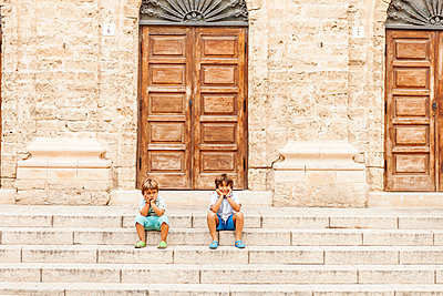 Two little boys sitting on stairs of an old building - p300m1205653 by Valentina Barreto
