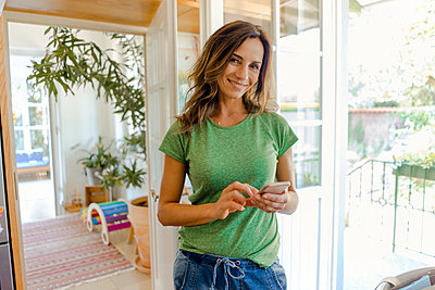 Portrait of smiling mature woman using cell phone at home - p300m2029640 von Kniel Synnatzschke