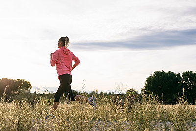 Woman running at agricultural field during sunny day - p300m2273498 by Andrés Benitez