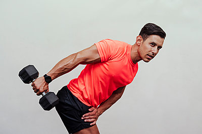 Male sportsperson bending while exercising with dumbbell by white wall - p300m2273990 by Eva Blanco