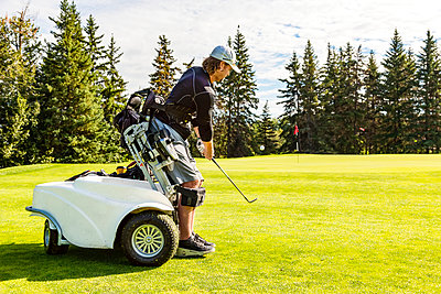 A physically disabled golfer chipping a ball onto the green and using a specialized golf assistance motorized hydraulic wheelchair; Edmonton, Alberta, Canada - p442m2019728 by LJM Photo