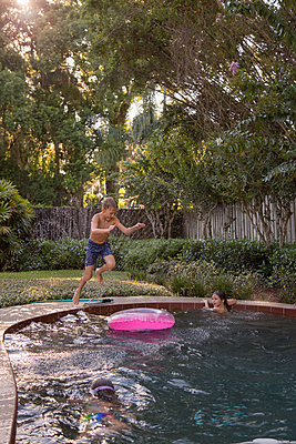 Children swimming in garden pool, young boy jumping in, mid-air - p924m1493688 by Kinzie Riehm