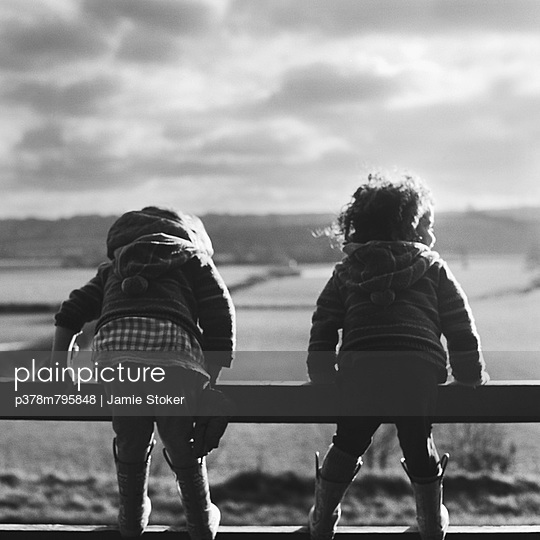 Two toddlers on fence - p378m795848 by Jamie Stoker