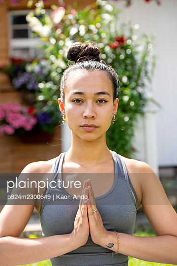 UK, London, Portrait of woman meditating in front of house - p924m2300649 by Kaori Ando