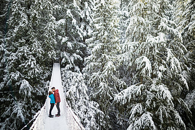 Full length of couple kissing while standing on footbridge amidst trees in forest at Lynn Canyon Park during winter - p1166m1576585 by Cavan Images