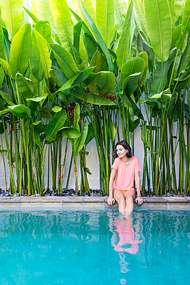 Young lady sitting at the pool side at private villa - p1166m2124270 by Cavan Images