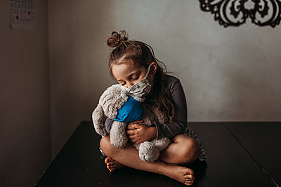 Young girl with mask on cuddling with masked stuffed animal - p1166m2207789 by Cavan Images