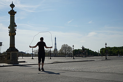 A young man plays with a skipping rope in place Concorde with Eiffel tower - p1610m2181518 by myriam tirler