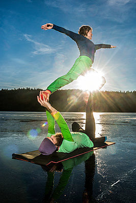 Couple doing yoga on frozen lake - p312m1470654 by Fredrik Schlyter