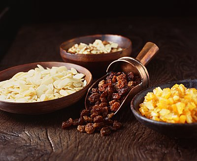 Chopped hazelnuts, raisins and dried orange in bowls - p429m1126007f by Diana Miller