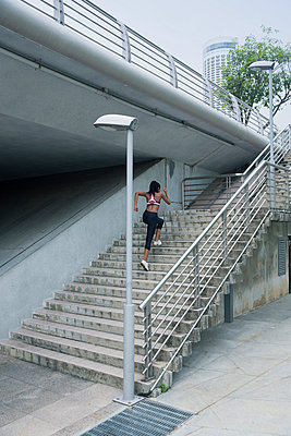 Mixed Race woman running up urban staircase - p555m1301938 by Hello Lovely