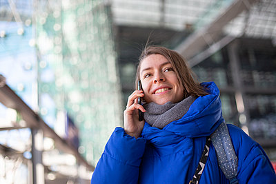 Young woman is talking on the mobile phone - p975m2245771 by Hayden Verry