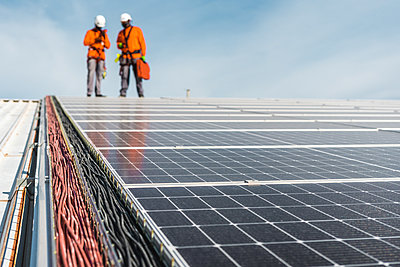 Solar panel installation with unrecognizable technicians on top - p1166m2268623 by Cavan Images