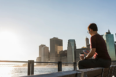 USA, Brooklyn, woman with coffee to go sitting on bench looking at smartphone - p300m1205774 by Uwe Umstätter