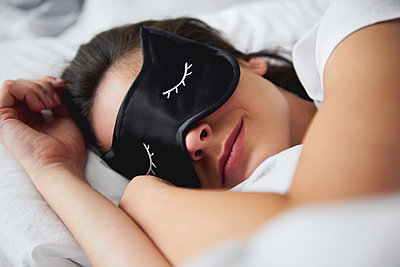 Portrait of young woman with sleep mask in bed - p300m2041658 von gpointstudio
