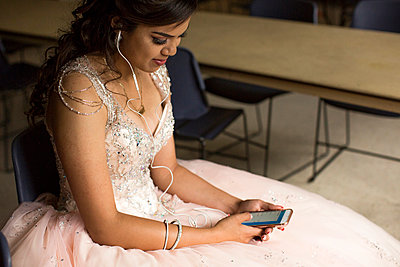 Smiling Hispanic girl listening to cell phone with earbuds - p555m1491509 by Adam Hester