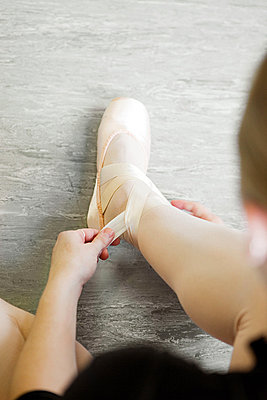 Ballerina tying ribbon on slipper - p9245552f by Image Source