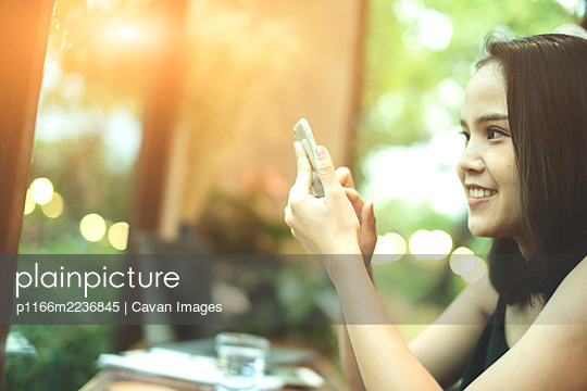 Asia woman using smartphone,mobile phone working,playing with re - p1166m2236845 by Cavan Images
