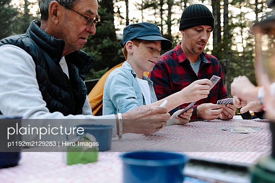 Multi-generation family playing cards at campsite picnic table - p1192m2129283 by Hero Images
